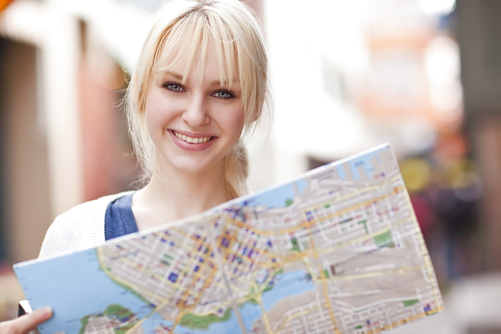 USA, Seattle, Smiling young woman holding map
