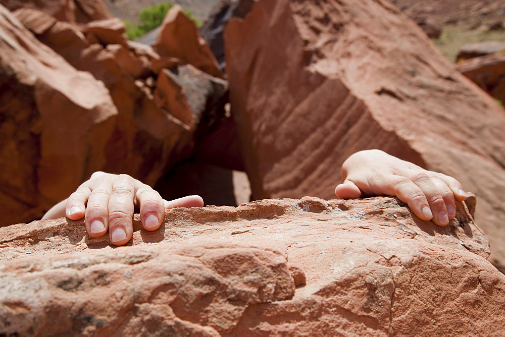 Young woman's hands on rocks