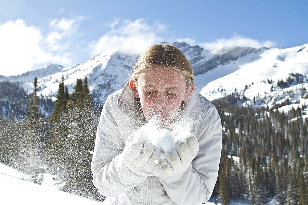 Girl (10-11) blowing snow in mountains