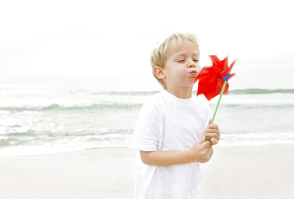 Boy (4-5) blowing on red pinwheel
