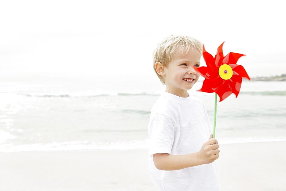 Boy (4-5) holding red pinwheel