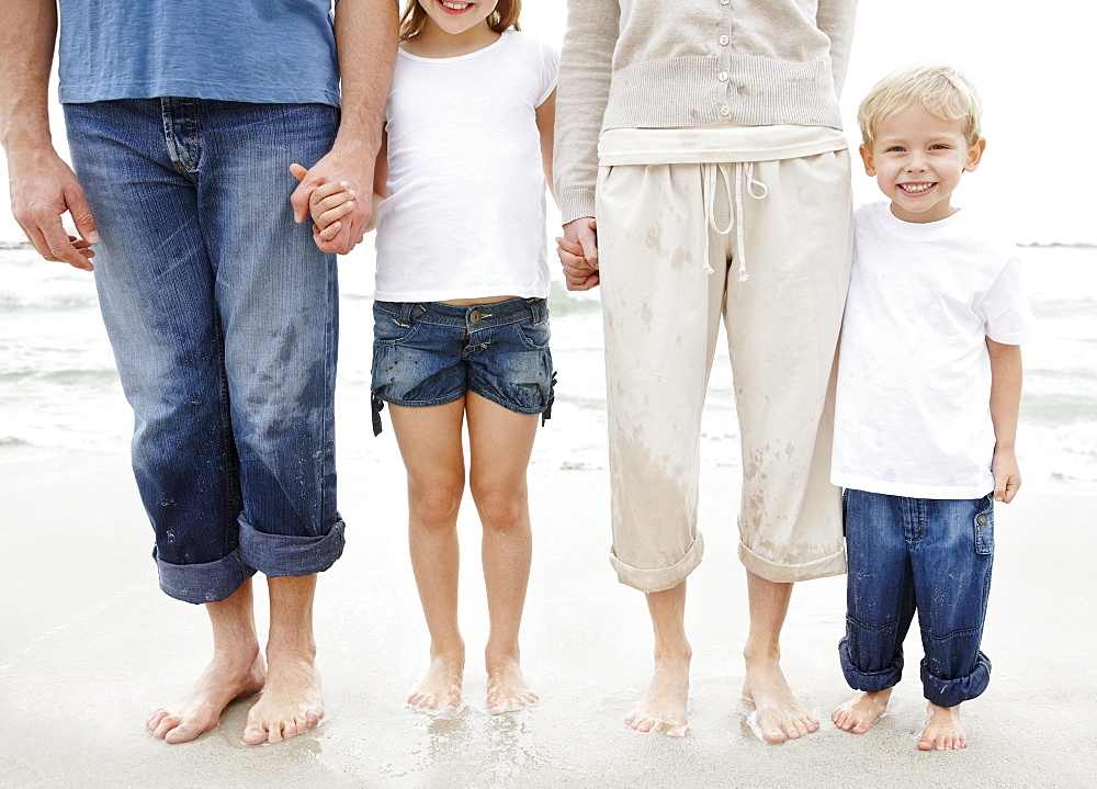 Family holding hands and posing at beach, midsection