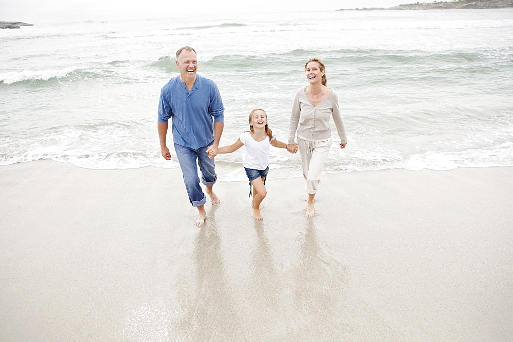 Smiling family holding hands and walking on beach