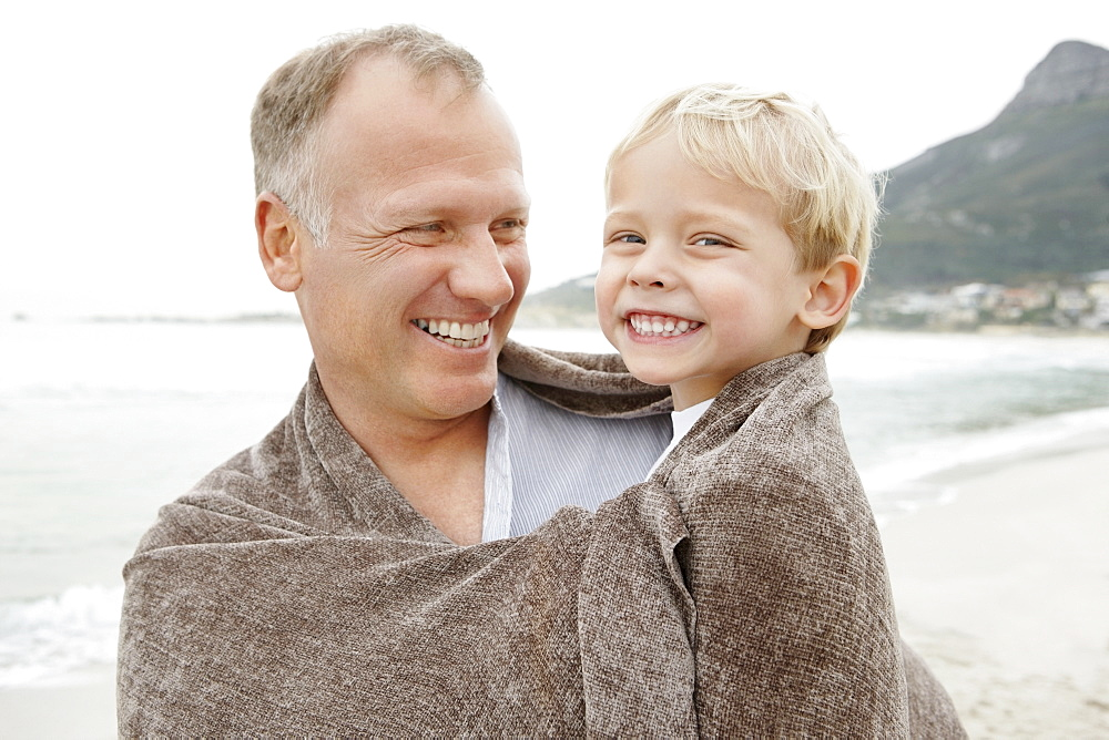 Father carrying son (4-5) on beach