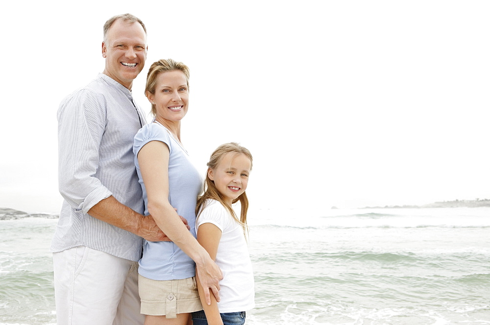 Smiling family standing at beach and looking at camera