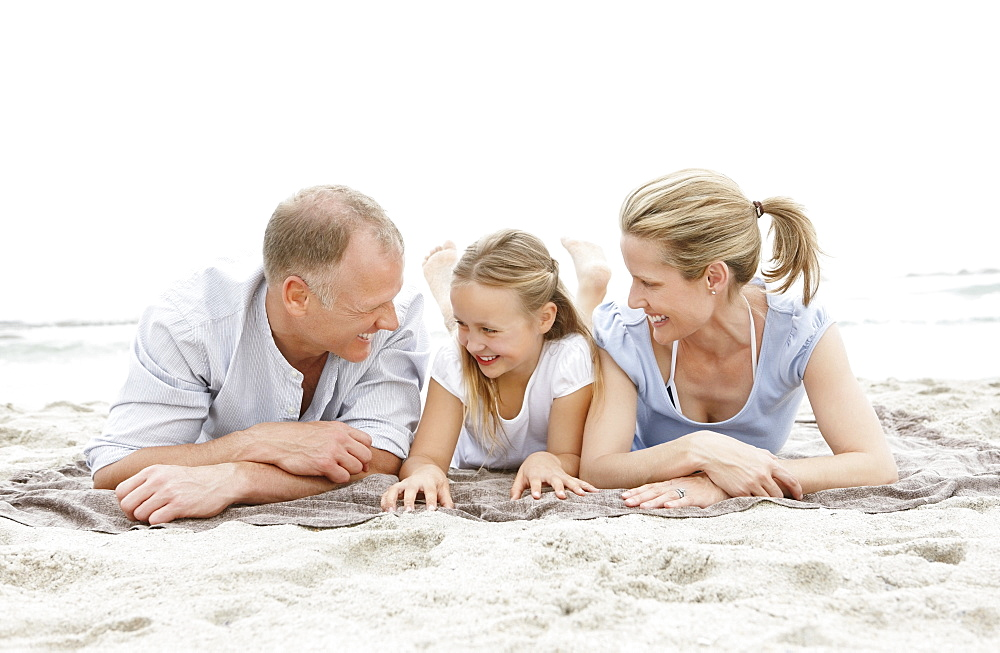 Two parents lying on beach with daughter (10-11)