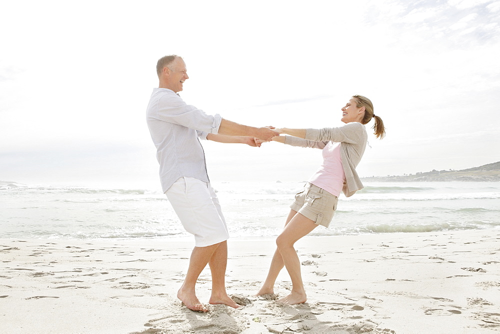 Portrait of couple playing on beach