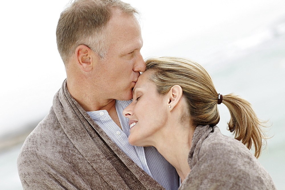 Portrait of couple wrapped in blanket on beach