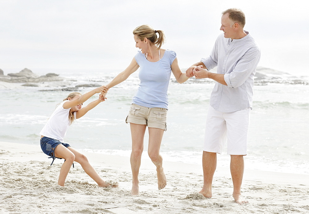 Girl (10-11) playing on beach with parents