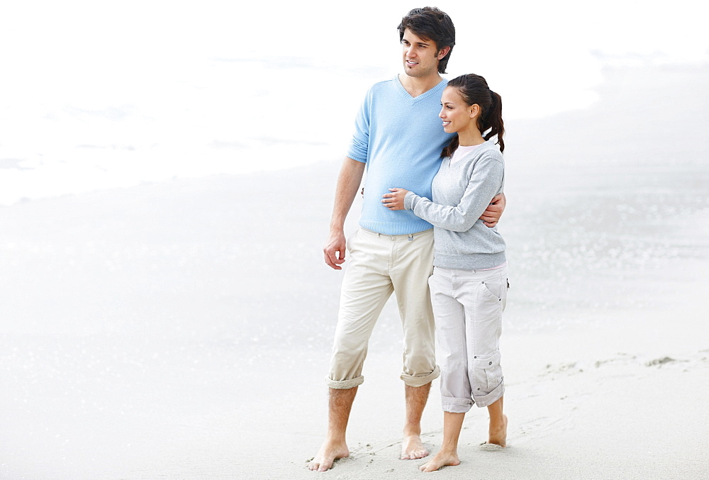 Couple walking barefoot on the beach