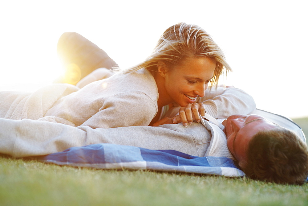 Couple lying down on picnic blanket