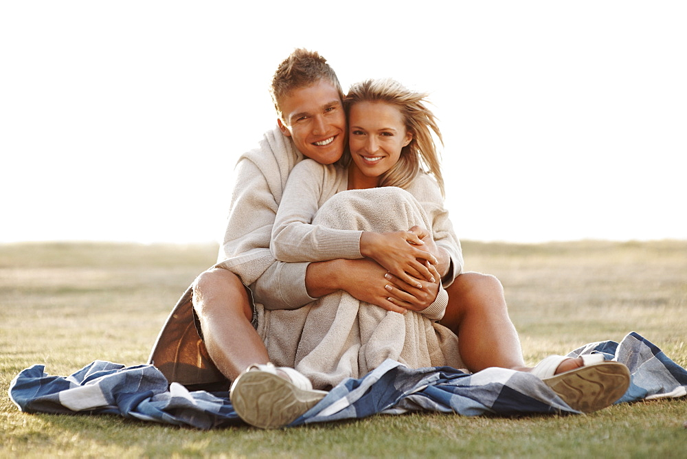 Couple sitting together in a field