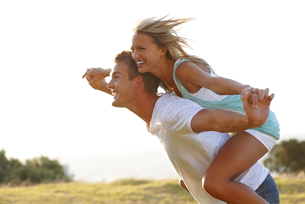 Man giving girlfriend a piggy back ride