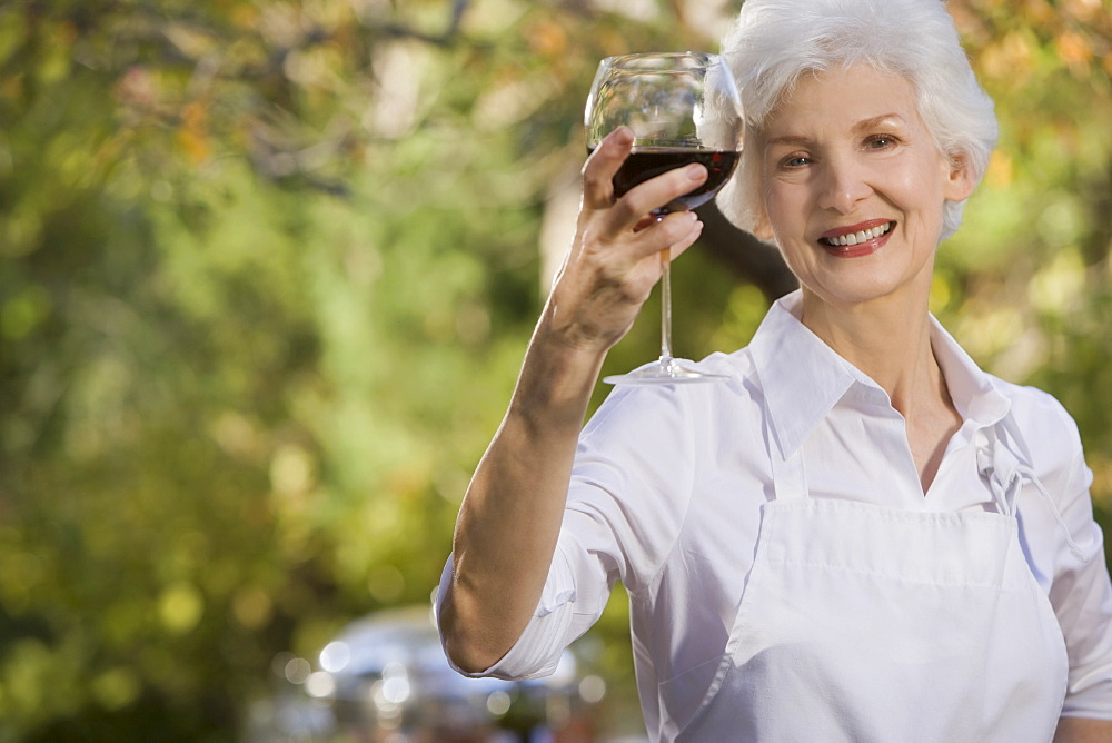 Senior woman holding glass of red wine, portrait