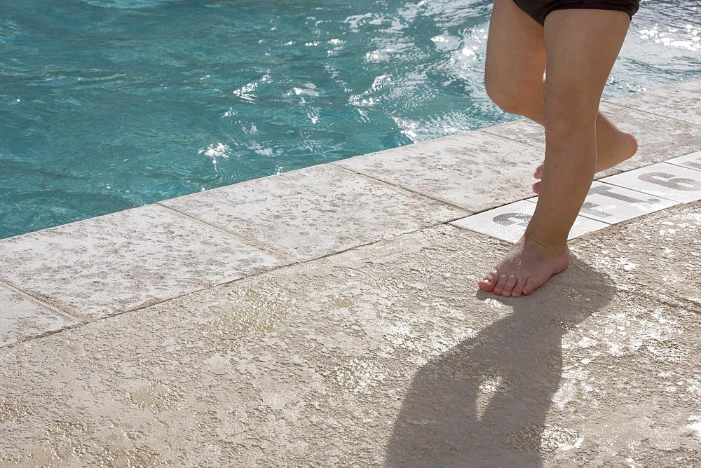 Baby boy walking at edge of swimming pool
