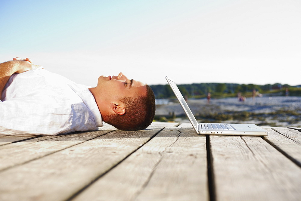 Man sleeping next to laptop on dock
