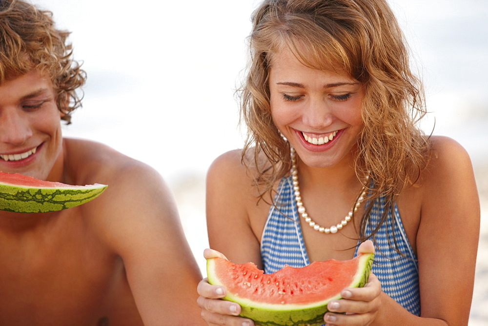 Young couple eating watermelon on beach