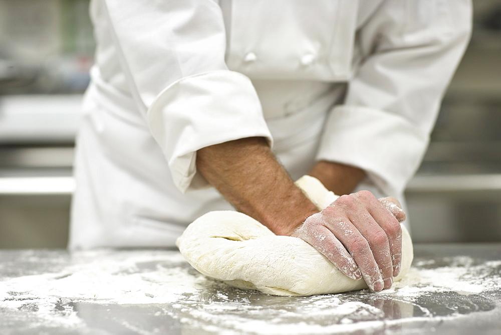 Baker kneading bread dough
