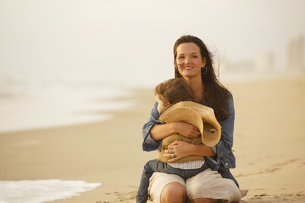Mother hugging child at beach