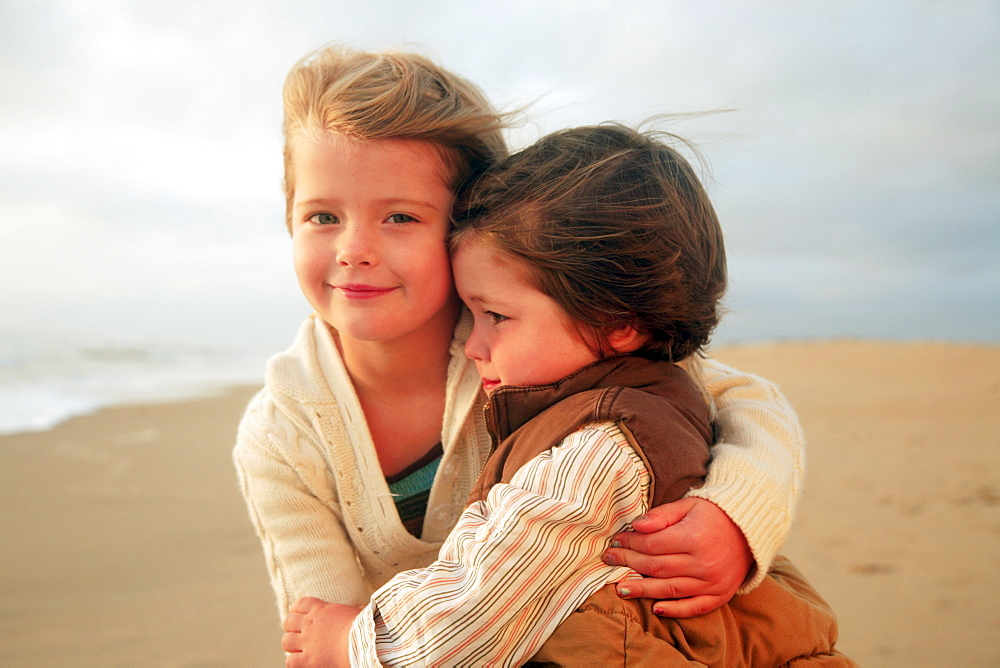 Sister and brother hugging at beach