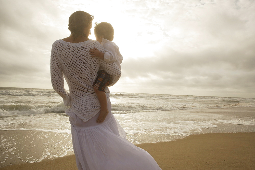 Mother holding child at beach