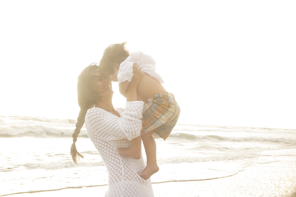Mother holding son at beach