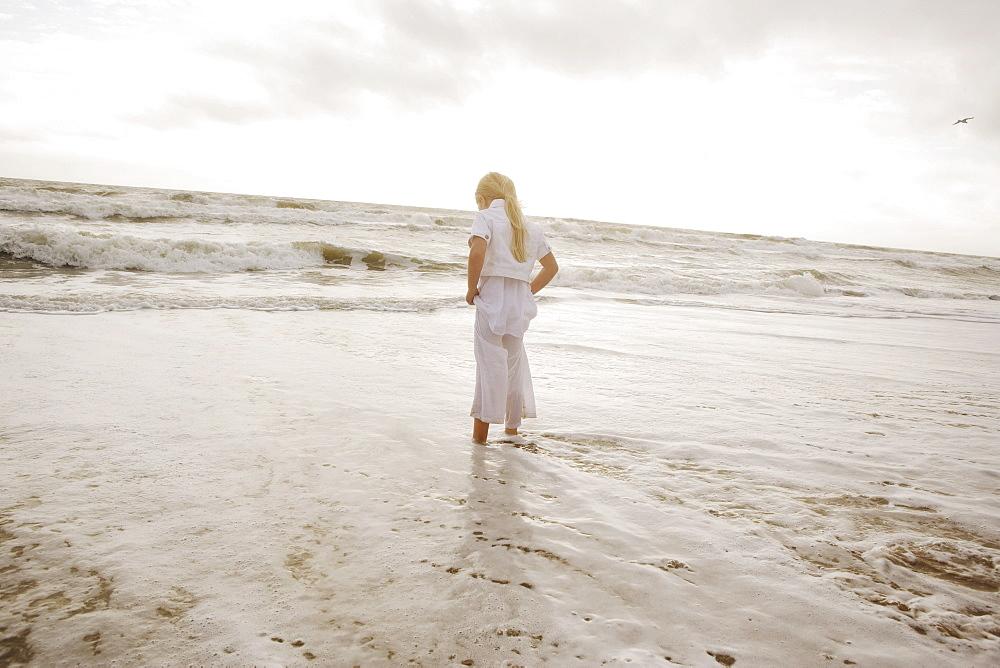 Girl standing in ocean surf