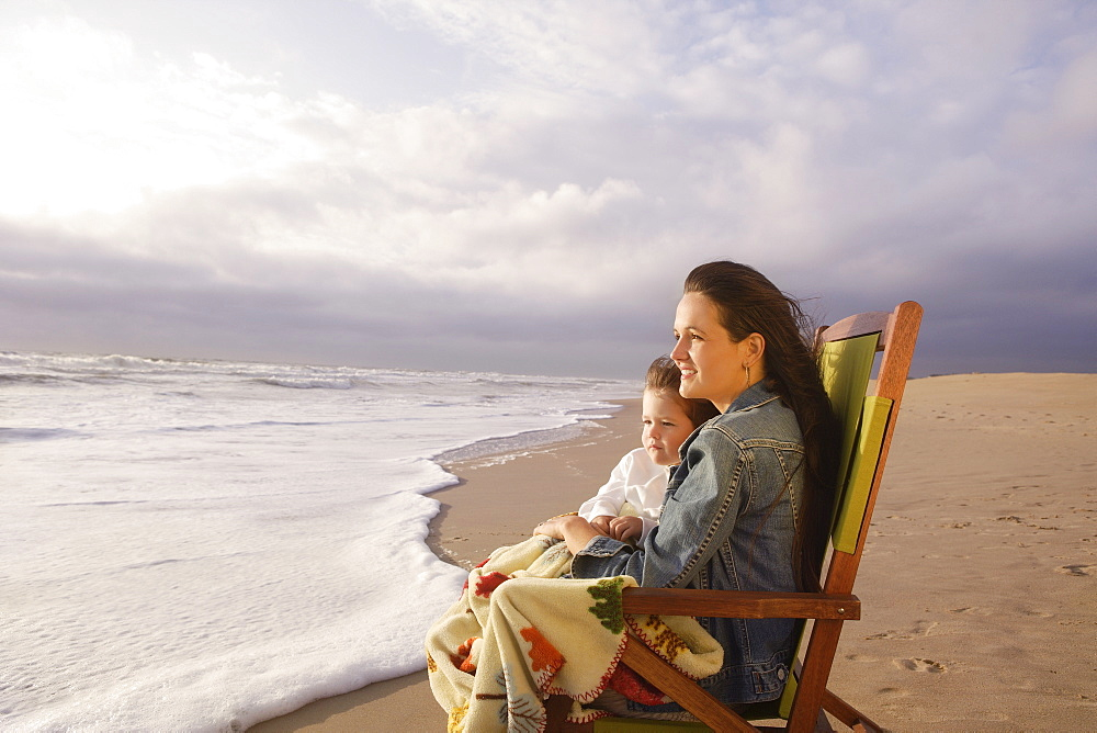 Mother and child sitting in beach chair