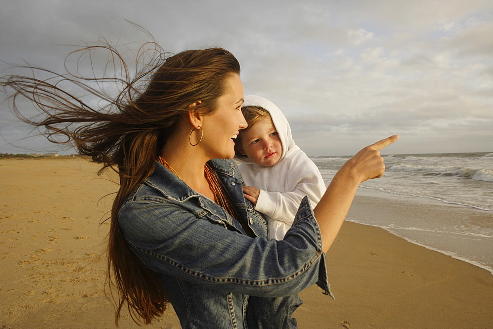Mother holding baby at beach