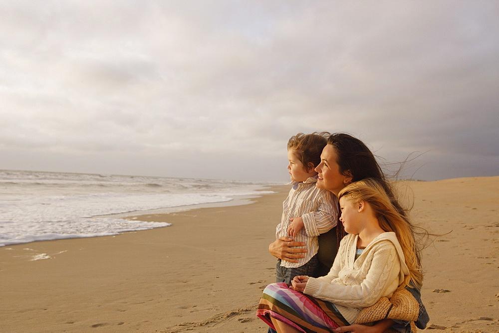 Mother hugging children at beach