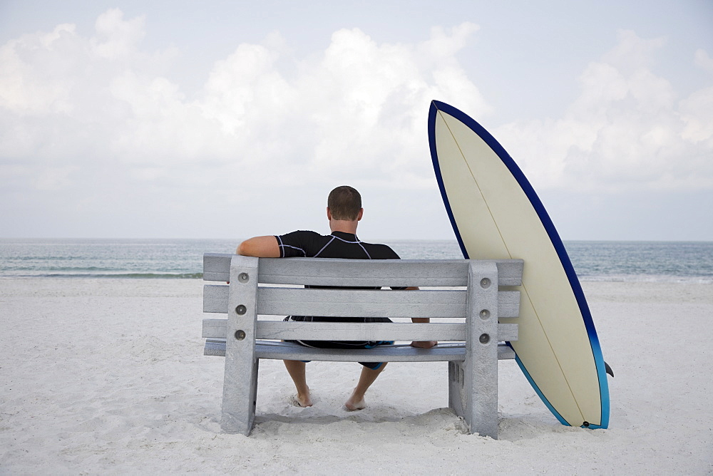 Surfer sitting on bench next to surfboard