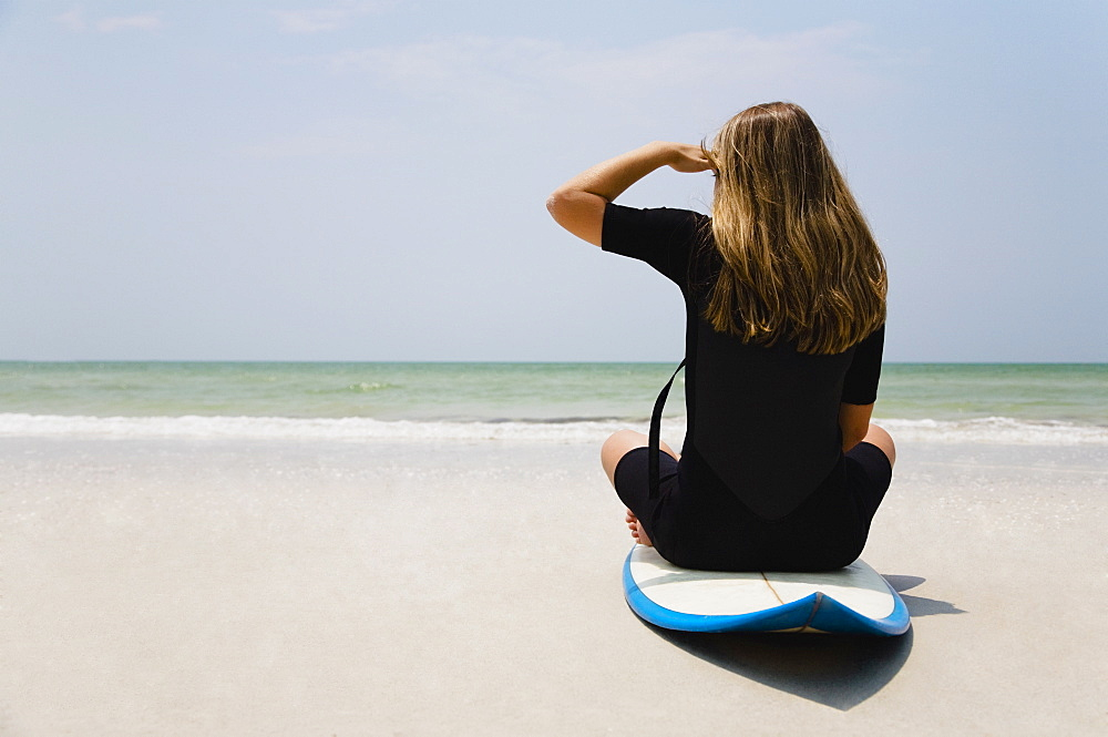 Girl sitting on surfboard, Florida, United States