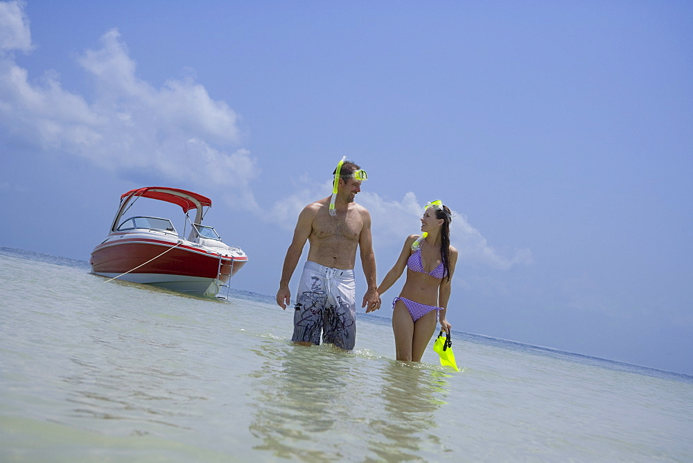 Couple with snorkeling gear walking in water, Florida, United States
