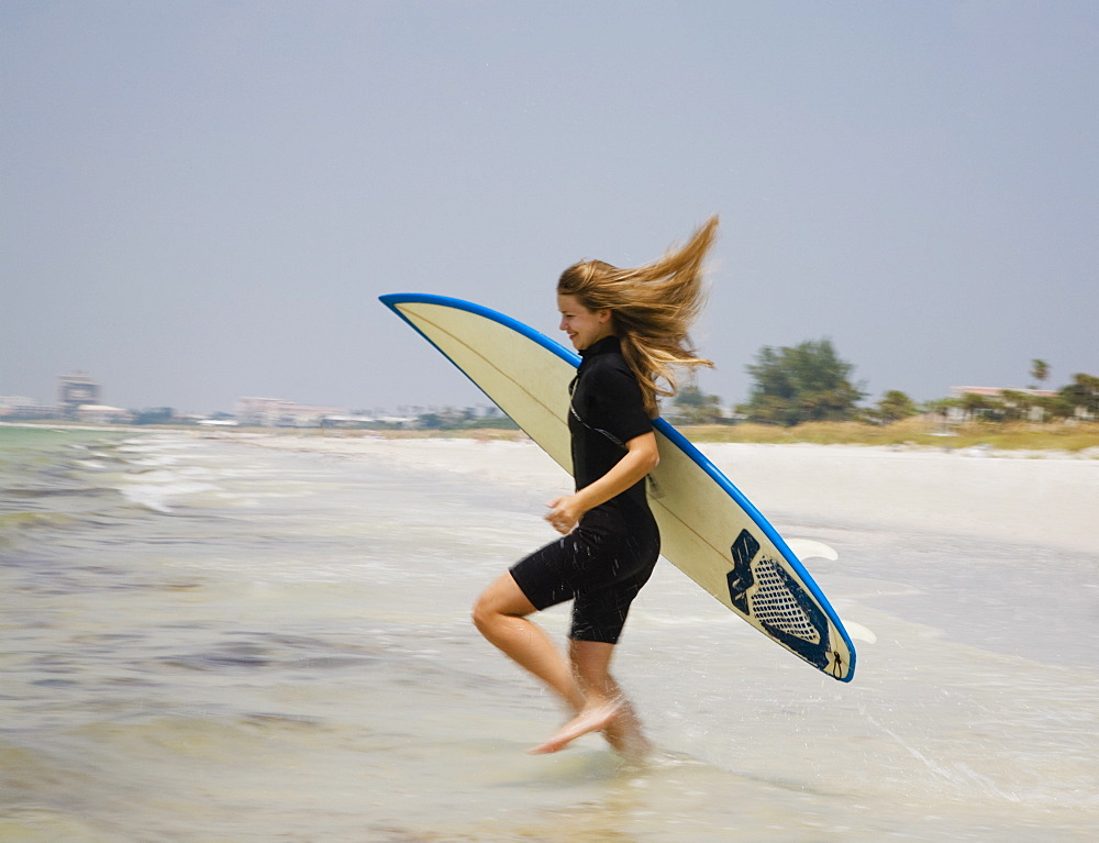 Girl running into water with surfboard, Florida, United States
