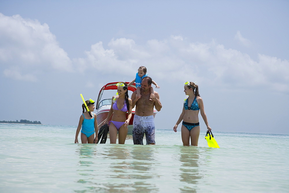 Family with snorkeling gear walking in water, Florida, United States