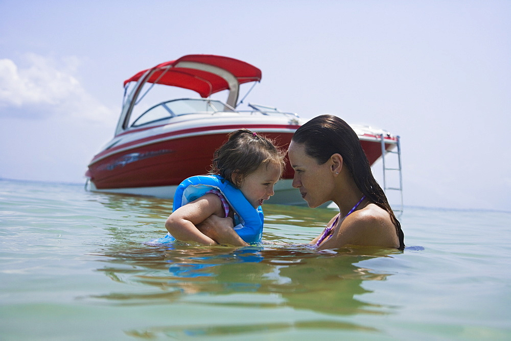 Mother helping daughter swim near boat, Florida, United States