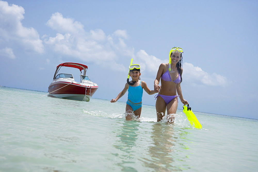 Mother and daughter with snorkeling gear walking in water, Florida, United States