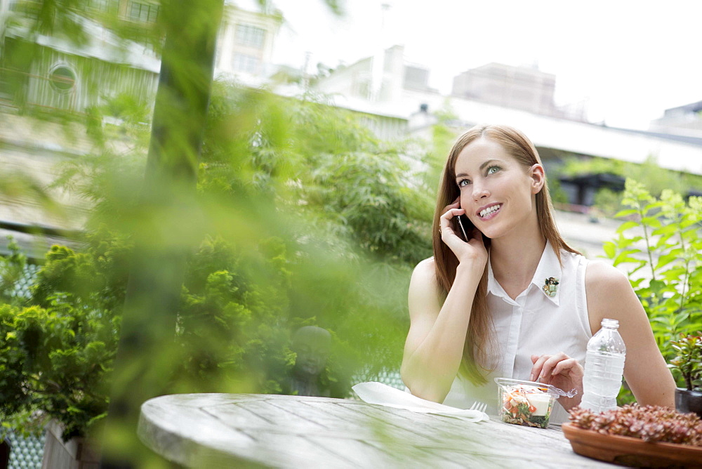 Portrait of young woman sitting on balcony and using mobile phone, New York City, USA