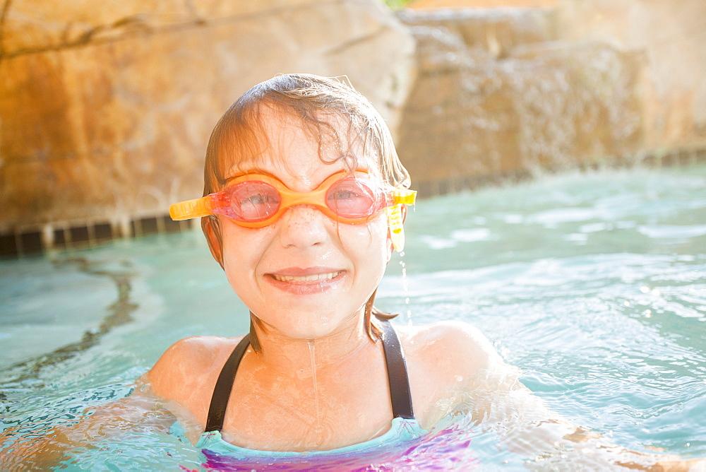 Girl (8-9) playing in swimming pool