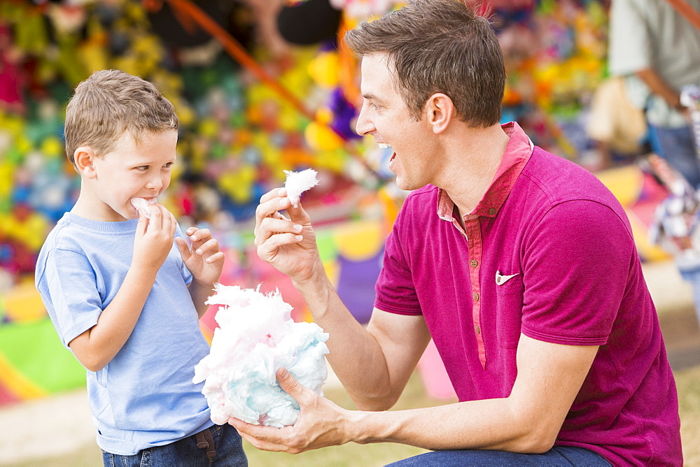 Happy father with son (4-5) in amusement park eating cotton candy, USA, Utah, Salt Lake City