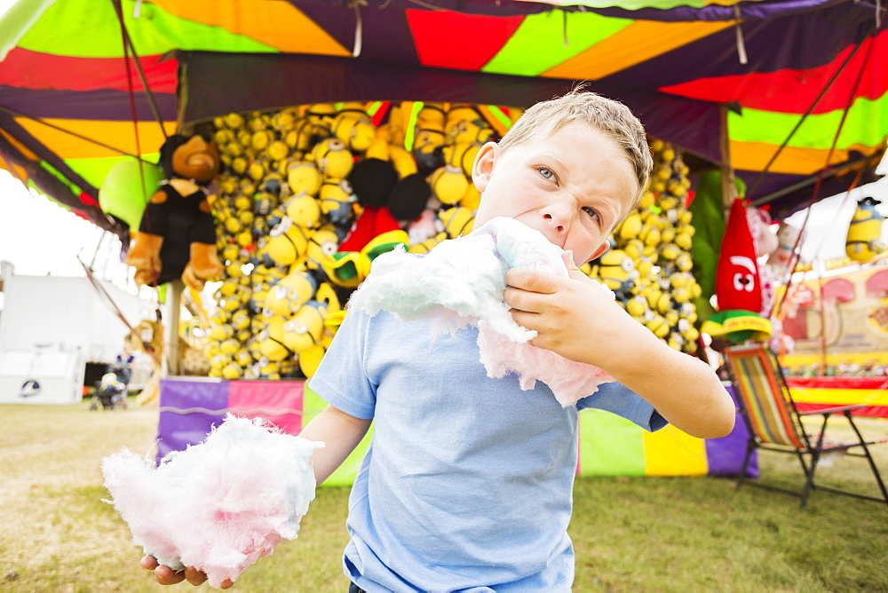 Boy (4-5) eating cotton candy in amusement park, USA, Utah, Salt Lake City