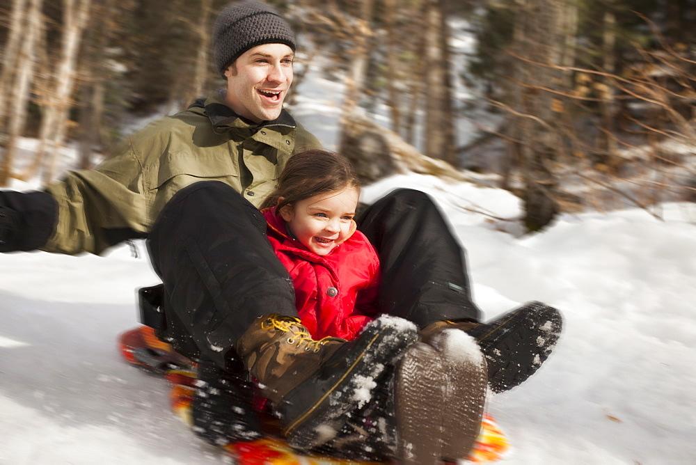 Young man sledding with girl (2-3), USA, Utah, Highland
