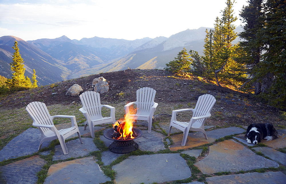 Dog lying down by fire pit and four empty chairs, Colorado, United States
