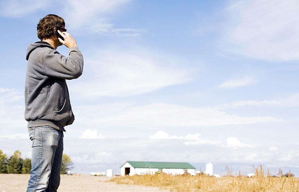Farmer in field using cell phone, Colorado, USA