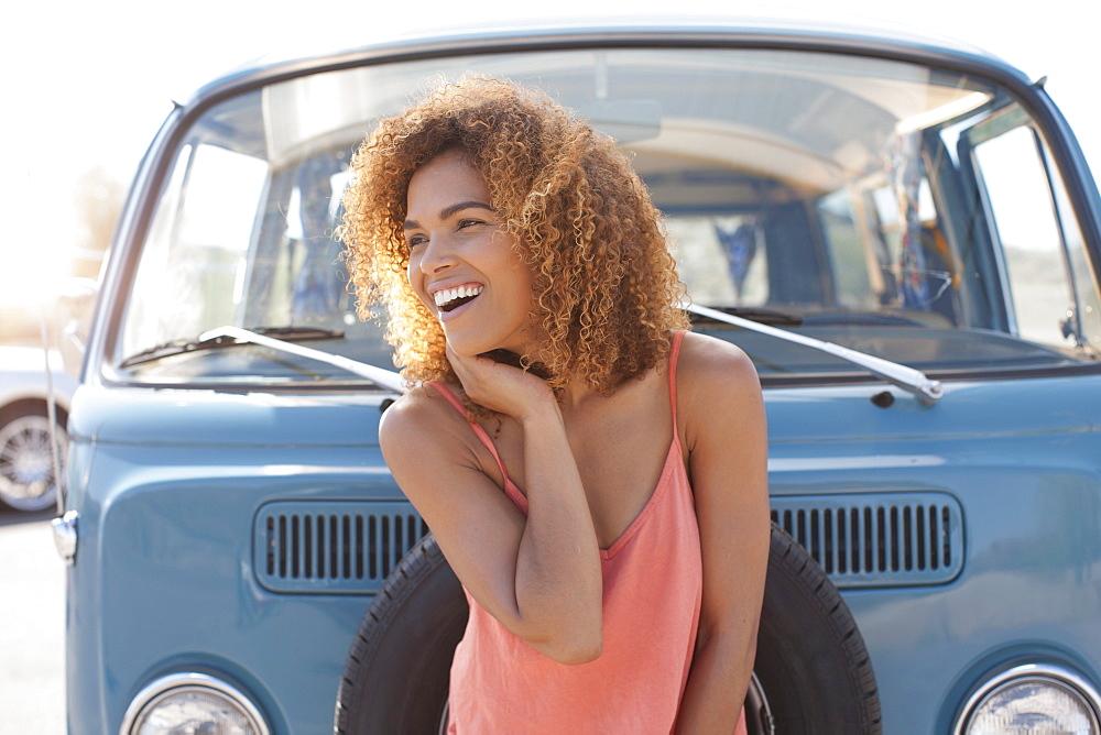 Smiling woman standing in front of van