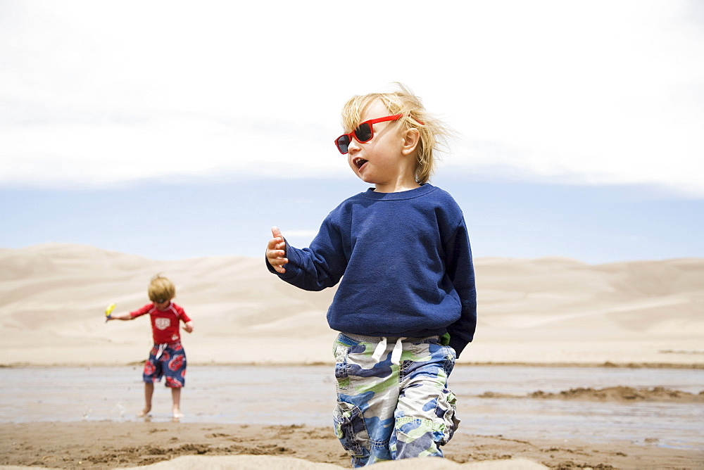 Toddler boys (2-3, 4-5) playing in water and sand dunes, Colorado, USA