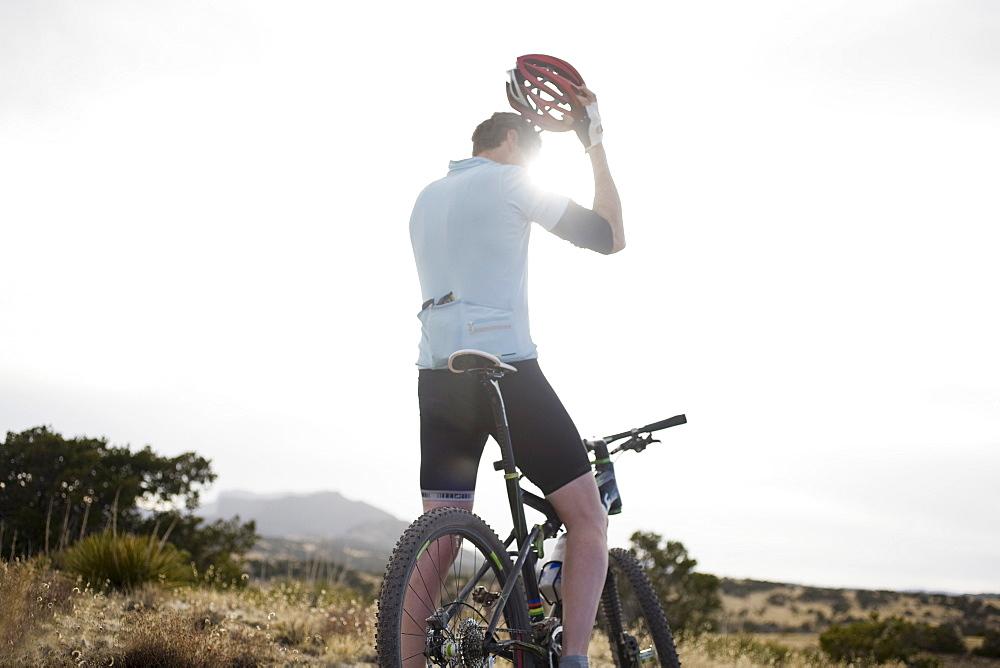 Man on mountain bike fixing helmet, Colorado, USA