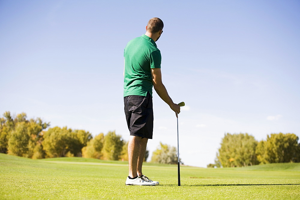 Rear view of man standing on golf course, Colorado, USA