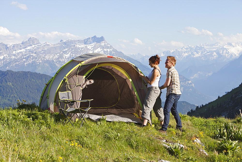 Switzerland, Leysin, Hikers pitching tent on meadow, Switzerland, Leysin