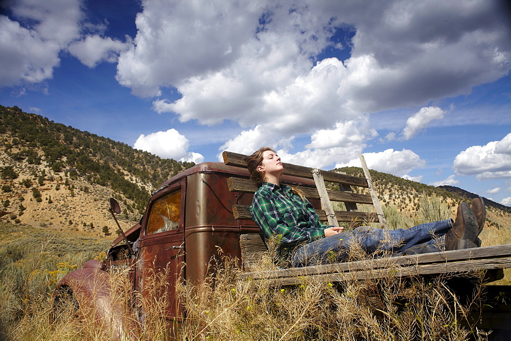 USA, Colorado, Woman resting on bed of abandoned truck in desert
